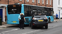 Drama as driver collides with two parked cars and bus