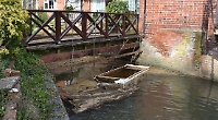 Homemade boat blocks sluice beneath flats