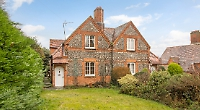 Grade II listed brick and flint cottage comes with south-facing back garden