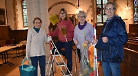 Volunteers clean church with brushes and beeswax