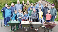 Pupils help parents clean up their outdoor classroom