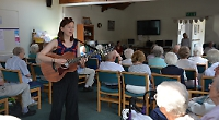 Folk singer entertains pensioners ahead of festival gig