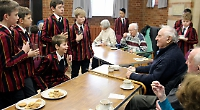 Boys entertain elderly with singing and chat