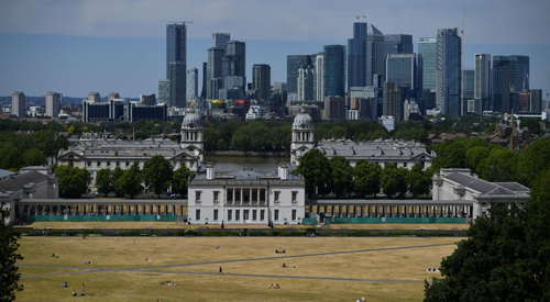 People relax as they take in the view of the London City sky line from Greenwich Park.
